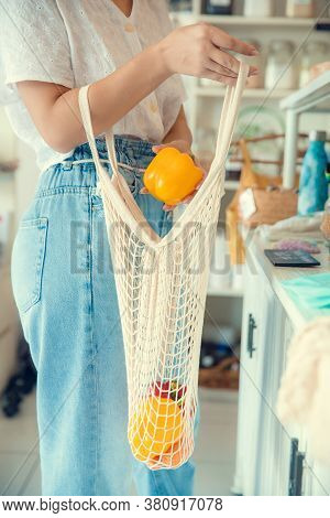 Woman Hand Holding String Shopping Bag With Vegetables And Fruits In Eco Shop. Vegetables In Eco-fri