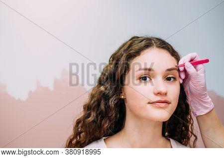 Eyebrow Master Makes An Eyebrow Correction To A Young Woman. Henna Eyebrow Coloring Procedure In A B