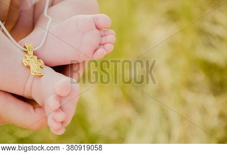Banner. Baptism Of The Child. Baby Baptism Ceremony. Legs And Cross In The Frame. High Quality Photo