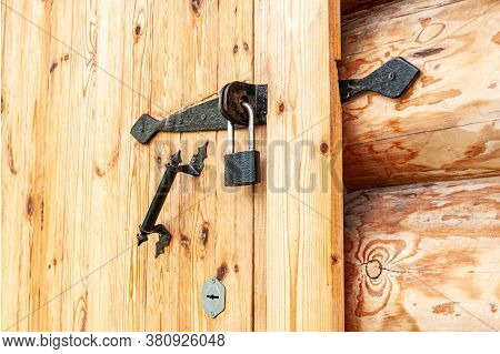 Small Black Padlock On The Wooden Door Of The Log House