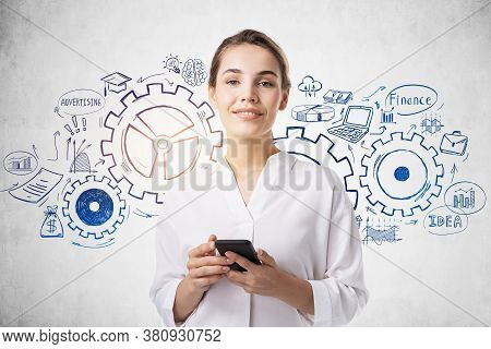 Smiling Young European Businesswoman With Smartphone Standing Near Concrete Wall With Creative Gears