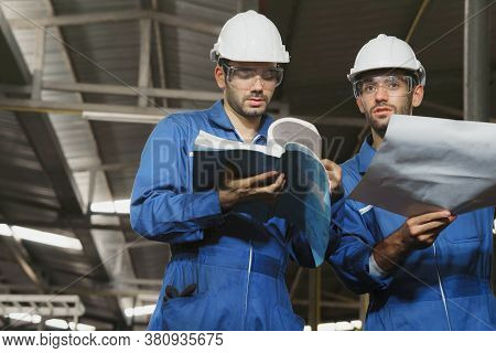 Factory Engineer Or Mechanical Worker With White Safety Helmet Holding The Manual And Consulting On