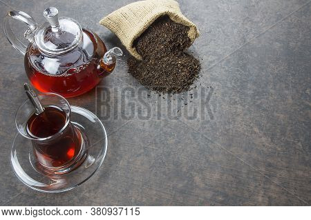 Glass Turkish Brewed Black Tea And Glass Teapot With Dry Black Tea In Burlap Sack On Black Rustic Ta