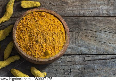 Turmeric Peeled Root And Turmeric Powder In Wooden Spoon Or Bowl On Wooden Rustic Background, Health