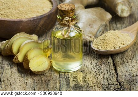 Glass Bottle Of Essential Ginger Oil, Ginger Root And Powder On Wooden Rustic Background. Healthy Fo