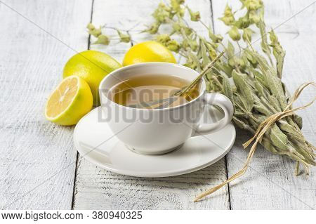 White Cup Of Herbal Sage Tea With Dried Sage Leaves And Lemon On White Wooden Rustic Background. Her