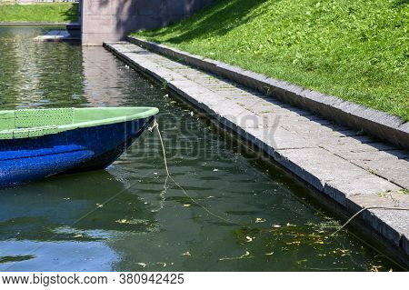The Bow Of The Wooden Boat Is Blue And The Pond. The Boat Is Tied With A Rope Near The Shore. Moscow