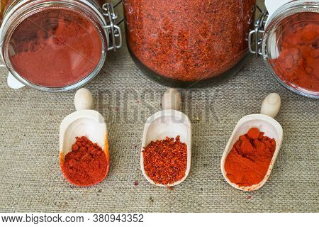 Smoked Hot Paprika, Sweet Paprika And Chopped Paprika In Wooden Scoops And Jars On Background