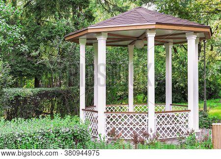 White Wooden Gazebo In A Summer Park. Garden Pergola.