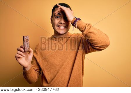 Young brazilian man eating healthy energy bar with protein over isolated yellow background stressed with hand on head, shocked with shame and surprise face, angry and frustrated. Fear and upset