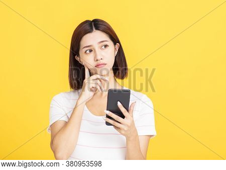 Young Asian Woman Holding Mobile Phone And Looking Away