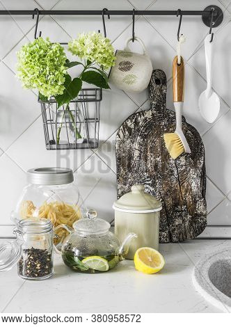 Cozy Scandinavian Style Kitchen Interior - Wooden Cutting Board, Dishes, Teapot With Green Tea On Th