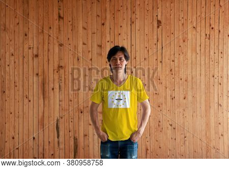 Man Wearing Rhode Island Flag Color Shirt And Standing With Two Hands In Pant Pockets On The Wooden
