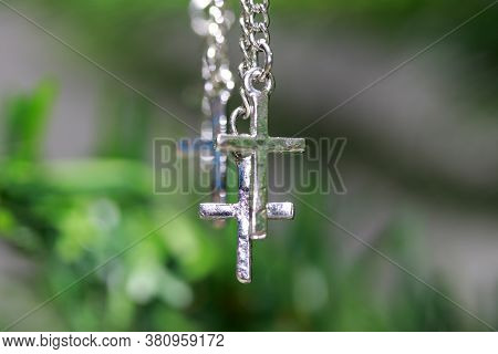 Metal Crucifix Bracelet Hanging On The Branches Of Tree. Concept Of Faith And Belief.