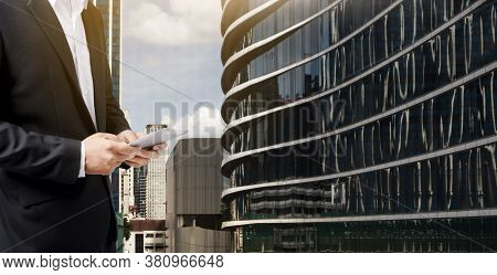 Businessman Working Online With A Digital Tablet With Office Building Background.