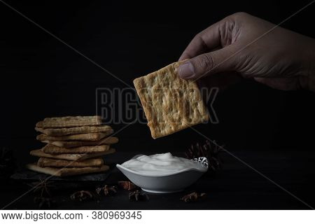 Salted Cracker Held By Hand With White Plain Yogurt, Pile Of Crackers On A Black Background