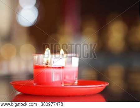 Red Candles In Clear Glass Lit On The Candle Holder At Temple, Candlelight