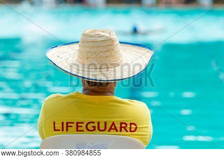 Swimming Pool Lifeguard Man In Yellow Lifeguard Shirt And Straw Hat On Duty At A Swimming Pool