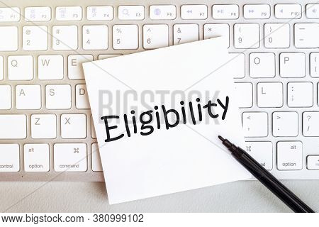Piece Of Paper With Text Eligibility On The Keyboard On A White Background With A Black Felt-tip Pen
