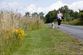Sporty woman and dog jogging along a road in summertime poster