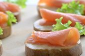 Closeup of a sandwich with smoked salmon butter and lettuce leaf. Shallow dof. poster