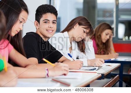 Portrait of teenage boy sitting with friends writing at desk in classroom