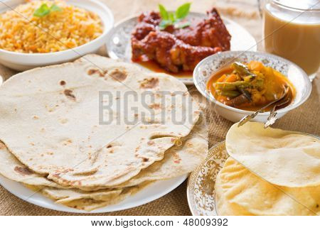 Chapatti roti or Flat bread, curry chicken, biryani rice, salad, masala milk tea and papadom. Indian food on dining table.  poster