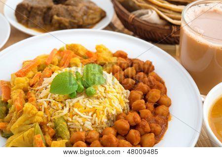 Indian food biryani rice, mutton curry, chapatti, milk tea and dal. Indian dining table.