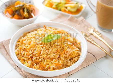 Indian vegetarian food. Biryani rice, curry dhal and milk tea on dining table.  poster