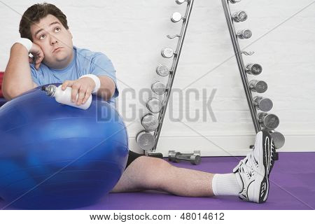 Portrait of a wistful overweight man sitting on floor with exercise ball in health club poster