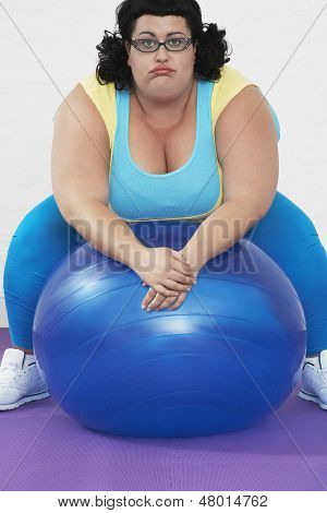 Portrait of an overweight woman sitting on exercise ball in healthclub