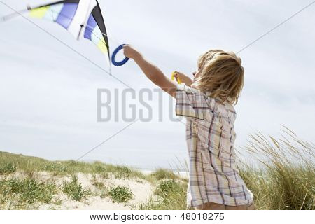 Side view of preadolescent boy flying kite on a windy beach