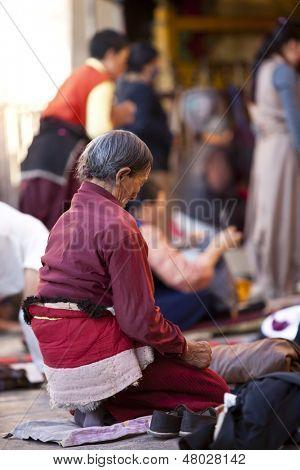 LHASA, TIBET-OCTOBER 08: An old female Tibetan buddhist pilgrim is kneeling and praying in front of Jokhang Temple on October 08, 2011 in Lhasa, Tibet.