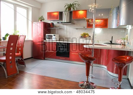 Interior of modern kitchen with a bar counter in red tones