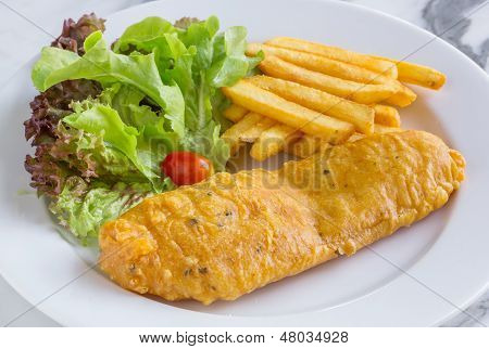 Fish and chip in white dish served with lettuce and small tomato poster
