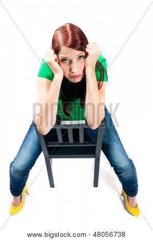 Woman is sitting on a Chair in the Studio and is demotivated or frustrated, even clueless or bored