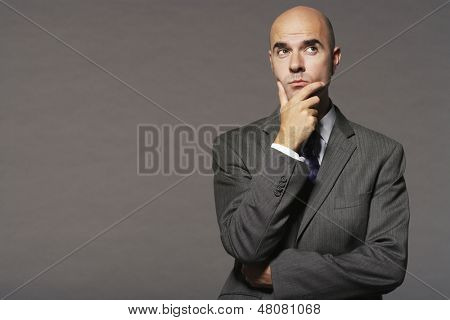 Bald businessman with hand on chin thinking against gray background