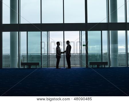 Side view of two silhouette businessmen shaking hands in the airport lobby