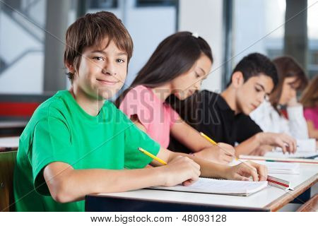Portrait of happy teenage boy with friends studying at desk in classroom