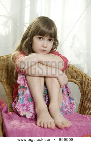 Little Cute Dreaming Girl Sitting On Chair At Window
