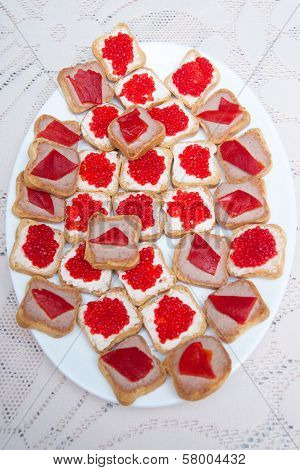Red caviar sandwiches on white festive table on a white oblong plate poster
