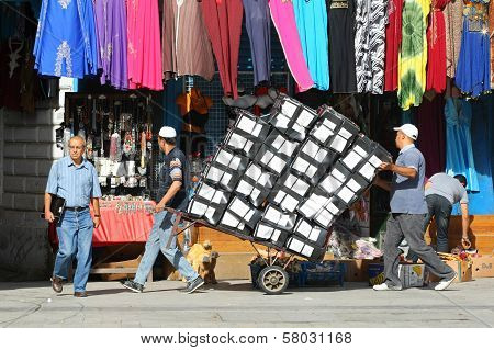 Two Men Pushing A Trolley