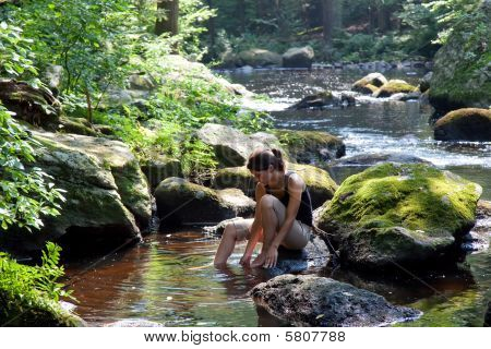 Woman Washing Her Feet In A Stream