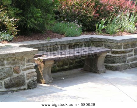 wood and concrete bench set in a niche along a stone retaining wall with garden behind poster