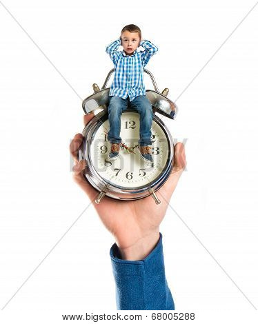 Tiny Boy Sitting On Antique Clock Covering His Ears