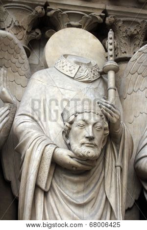 PARIS, FRANCE - NOV 05, 2012: Saint Denis holding his head, detail of Notre Dame cathedral. The Portal of the Virgin, dedicated to the patroness of the cathedral, was sculpted in the 1210s-1220s.