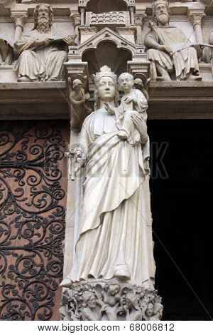 PARIS, FRANCE - NOV 05, 2012: Madonna with Child, architectural detail of Notre Dame cathedral. The Portal of the Virgin, dedicated to the patroness of the cathedral, was sculpted in the 1210s-1220s.