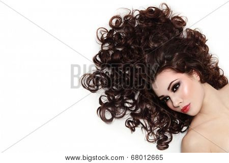 Young beautiful woman with dark long curly hair over white background