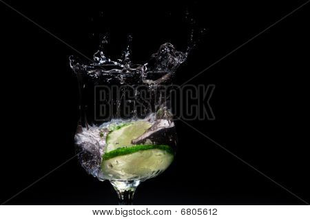 Fresh Lime Splashing Into Glass Of Liquid