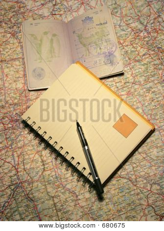Passport And Notebook On A Map
